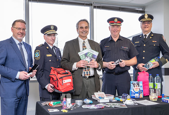 5 persons standing behind a table with various emergency kit items on it.